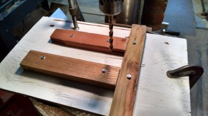 Three guide pieces screwed to a piece of plywood form a jig for drilling