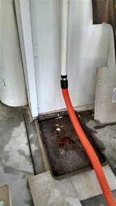 A Shop-Vac hose carries the water from the drain pipe out to the yard